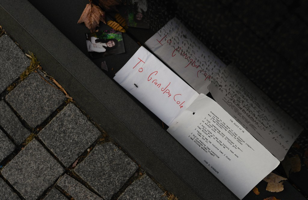 """A photo, a letter addressed to """"Grandpa Cole"""" and a chilling poem titled """"The Death of Me"""" were some of the items left recently at the Vietnam memorial. Photo by Ariel Min/PBS NewsHour"""