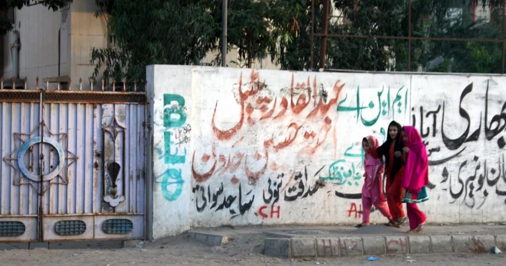 Girls walk by a wall of graffiti in Pakistan's port city Karachi. Photo by Larisa Epatko