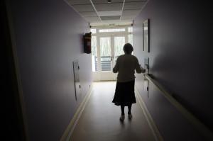 A woman, suffering from Alzheimer's desease, walks in a corridor on…