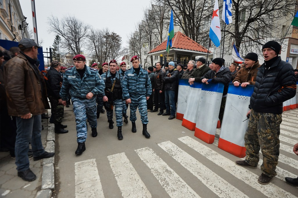 SIMFEROPOL, UKRAINE - MARCH 1: Pro-Russian supporters rally outside the Consulate General of the Russian Federation as Ukraine's Berkut riot police force march down the street on March 1, 2014 in Simferopol, Ukraine. According to media reports Russian soldiers have occupied the airport at nearby Sevastapol while soldiers whose identity could not be initially confirmed have stationed themselves at Simferopol International Airport in moves that are raising tensions between Russia and the new Kiev government. Crimea has a majority Russian population and armed, pro-Russian groups have occupied government buildings in Simferopol. (Photo by Aleksandr Miridonov/Kommersant Photo via Getty Images)