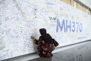 A woman writes a message on a banner for missing Malaysian Airlines Flight 370 at Kuala Lumpur International Airport (KLIA) in Sepang, Malaysia, in March 2014. Photo by Charles Pertwee/Bloomberg