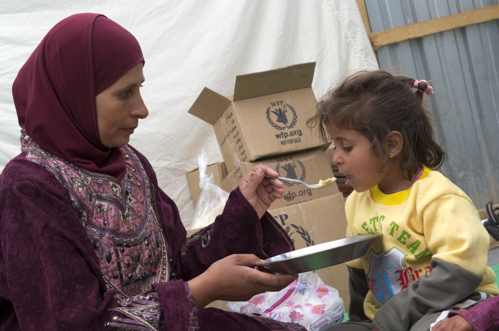 In this April 16, 2013, file photo, a mother feeds her child at the Zaatari refugee camp in Jordan, one of the countries where Syrians have fled due to the civil war. Photo by Rein Skullerud/U.N. World Food Program