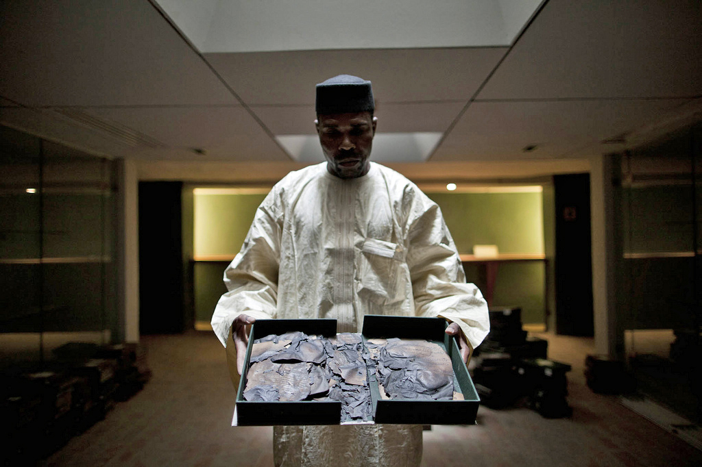 Abdoulaye Cisse, deputy director of the Ahmed Baba Institute of Higher Learning in Timbuktu, shows some of the estimated 4,000 ancient manuscripts that were burned after militant Islamists seized the northern part of Mali in 2012. About 300,000 other manuscripts were hidden and saved. Photo by Marco Dormino/U.N. mission in Mali