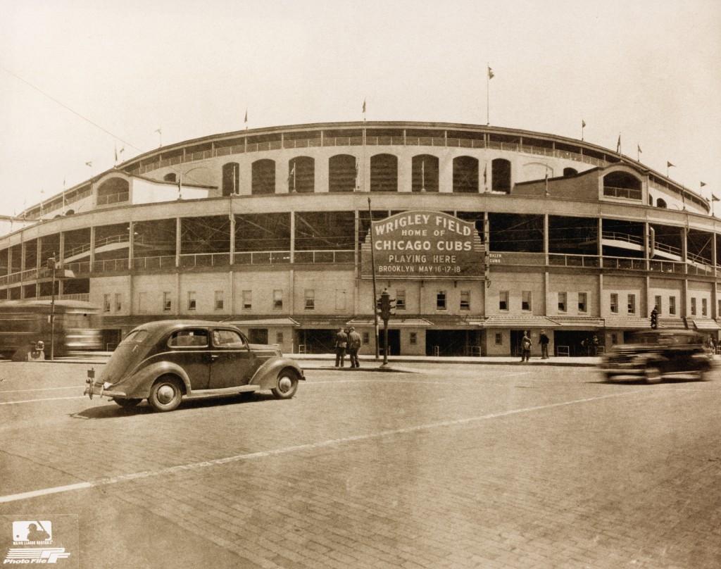 Exterior view of Wrigley Field as cars and pedestrians pass on the street in front of it, Chicago, Illinois, May 1939. Photo by Photo File/Getty Images