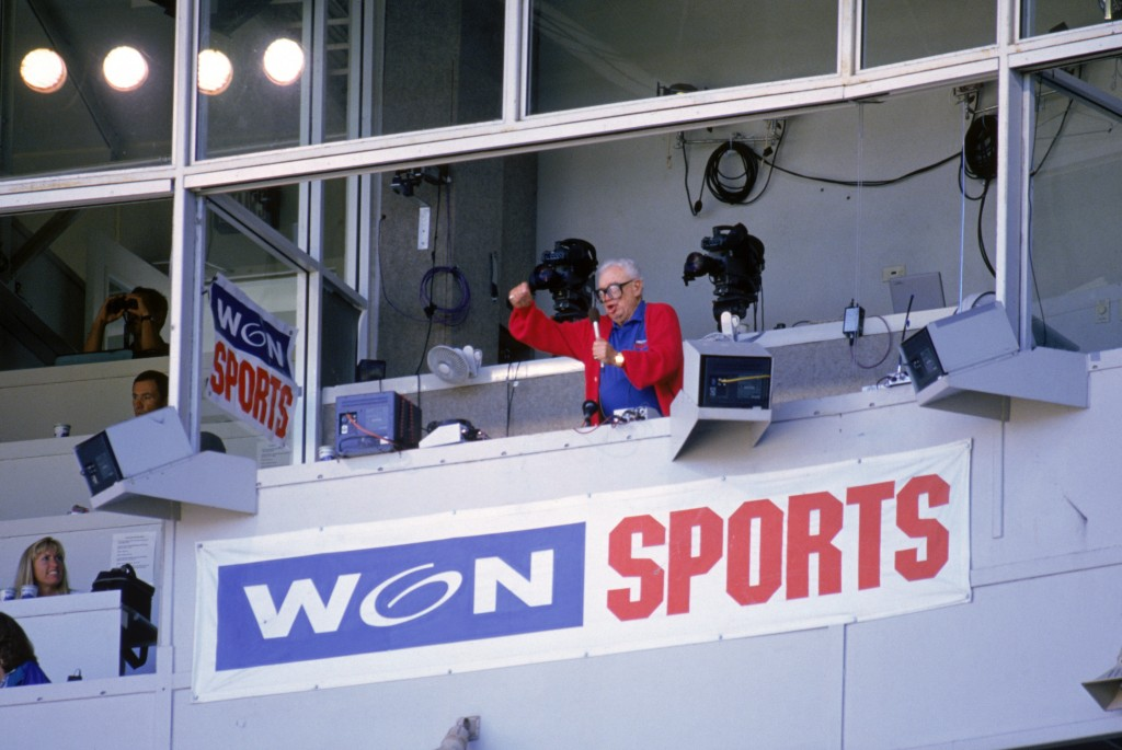 """Chicago Cubs baseball announcer and Baseball Hall of Fame inductee Harry Caray conducts fans singing """"Take Me Out to the Ball Game"""" from his television booth during the seventh inning stretch in a game against the Colorado Rockies at Wrigley Field on August 2, 1996. Photo by Jonathan Daniel/Getty Images"""