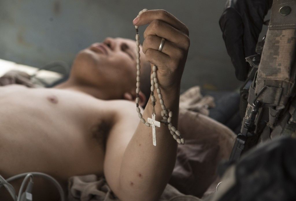 "Lance Cpl. Blas Trevino of the 1st Battalion, 5th Marines, clinches onto his Rosary beads as he is rescued onto a medevac helicopter from the U.S. Army's Task Force Lift ""Dust Off"", Charlie Company 1-214 Aviation Regiment after he got shot in the stomach outside Sangin, in the Helmand Province of southern Afghanistan, Saturday, June 11, 2011. Photo by Anja Niedringhaus/AP"