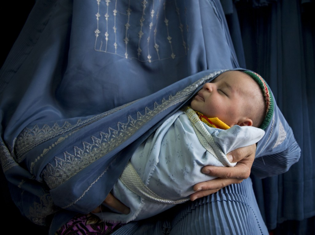 In this Thursday, April 11, 2013 photo, an Afghan woman holds her newly born baby wrapped in her burqa  as she waits to get in line to try on a new burqa in a shop in the old town of Kabul, Afghanistan. Photo by Anja Niedringhaus/AP