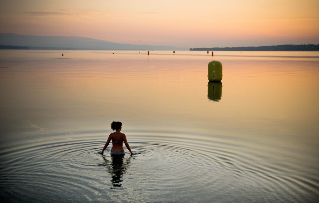 A woman takes a dip at sunrise in Lake Geneva, Geneva, Switzerland, Sunday, July 21, 2013. Photo by Anja Niedringhaus