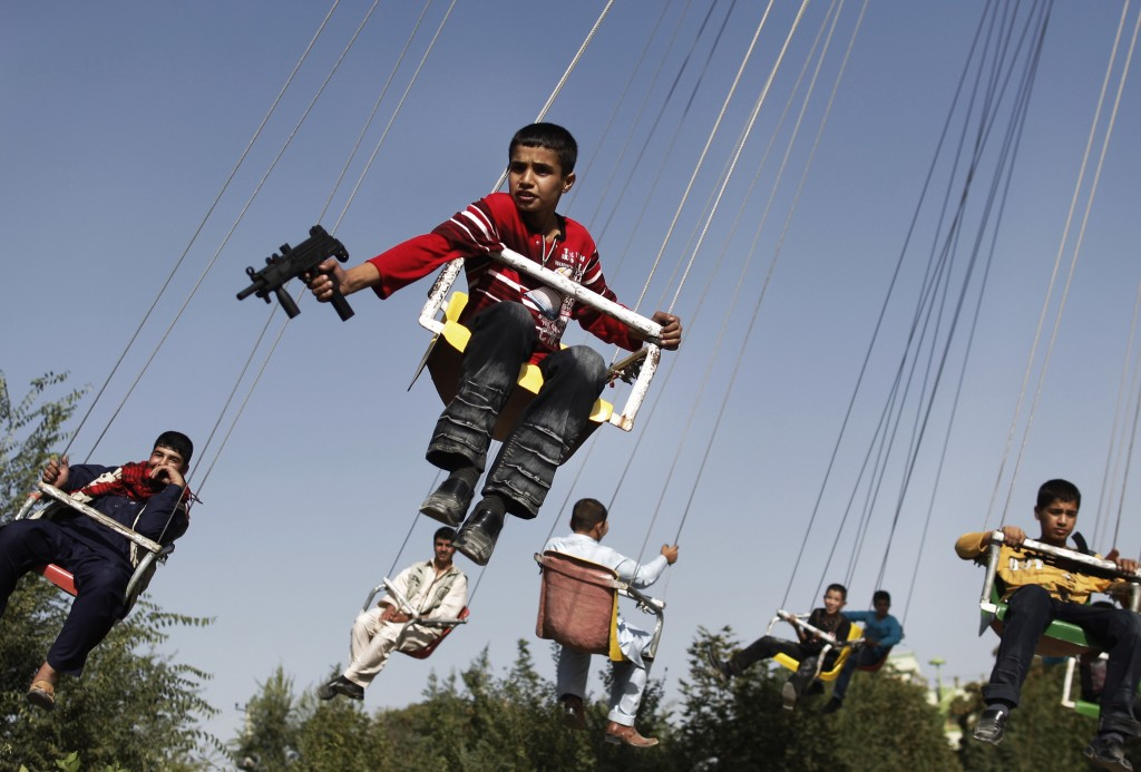 In this Sunday, Sept. 20, 2009 file photo, an Afghan boy holds a toy gun as he enjoys a ride with others on a merry-go-round to celebrate the Eid al-Fitr festival, in Kabul, Afghanistan. Photo by Anja Niedringhaus/AP