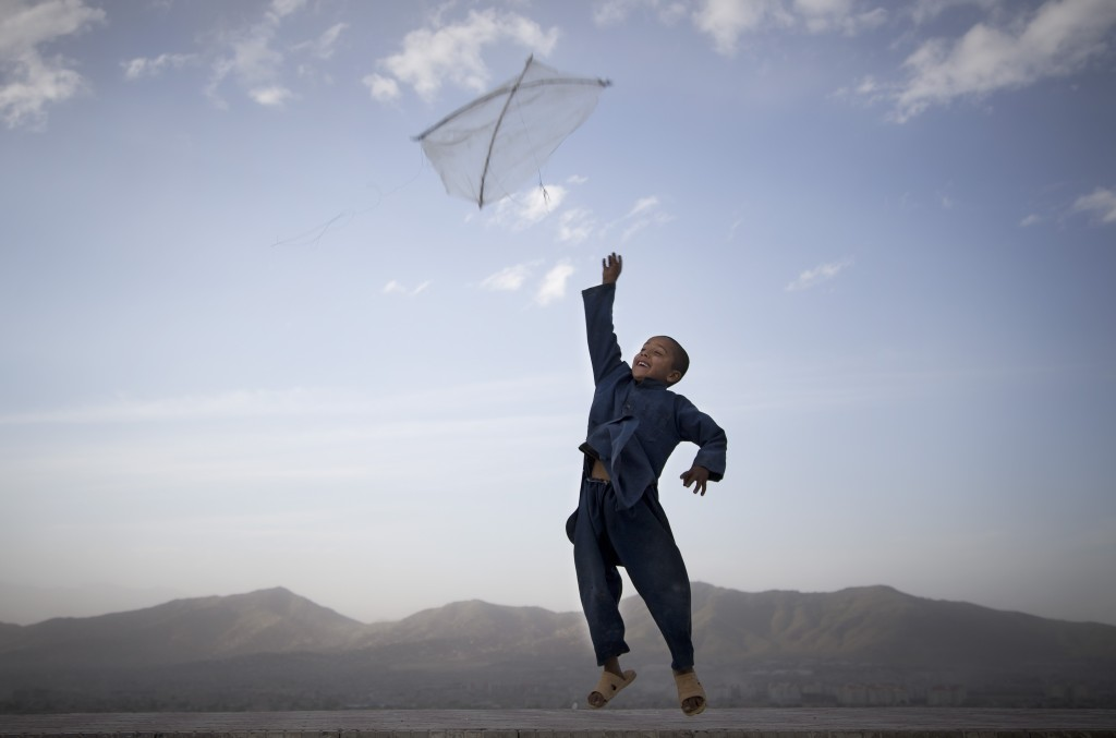 In this May 13, 2013 file photo made by Associated Press photographer Anja Niedringhaus, an Afghan boy flies his kite on a hill overlooking Kabul, Afghanistan.
