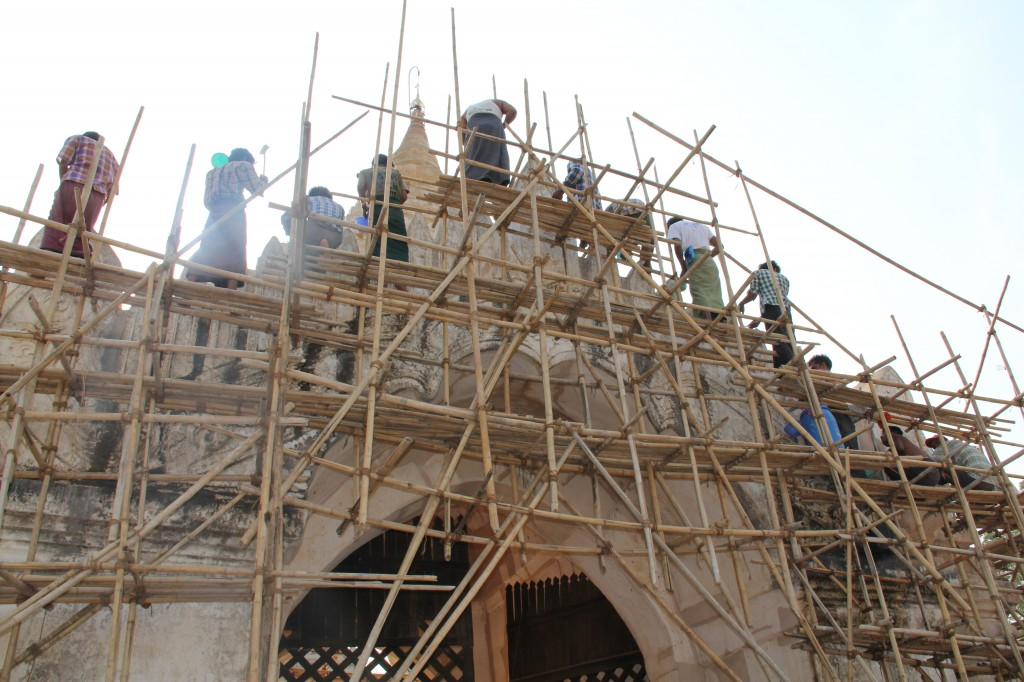 Internationally sanctioned conservation work is now being done in Bagan. Here laborers scrub the harmful limestone coating off an archway at the Ananda Temple.  It's part of a $22 million, five-year joint project between the governments of Myanmar and India. Photo by Mary Jo Brooks/PBS NewsHour