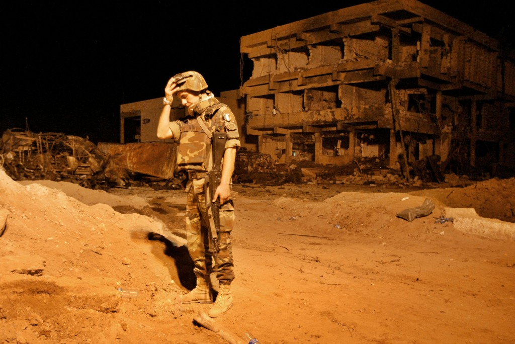 Under the harsh glare of spotlights, an Italian soldier stands  guard at the Carabinieri barracks in Nasiriyah where 33 people, including 19 Italians, were killed in a terrorist truck bombing in November, 2003. Photo by Anja  Niedringhaus/AP