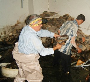 Dr. Harold Rhode examines some of the books that were left to soak underground. Photo by U.S. National Archives
