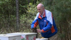 Ray Goldwire uses a smoker to gain access to his bee hives at his retirement community in Gainesville, Fla. Video still by Steve Mort/PBS NewsHour