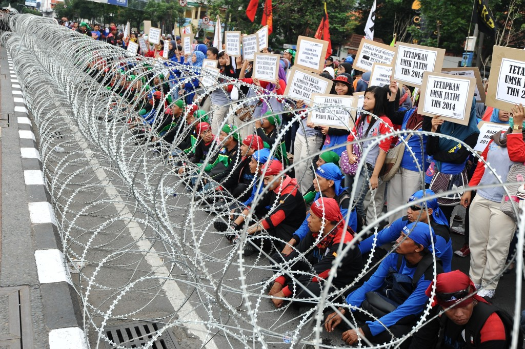 Indonesians workers sit behind barbed-wire during a protest demanding higher wages in Surabaya, Indonesia. Photo by Robertus Pudyanto/Getty Images