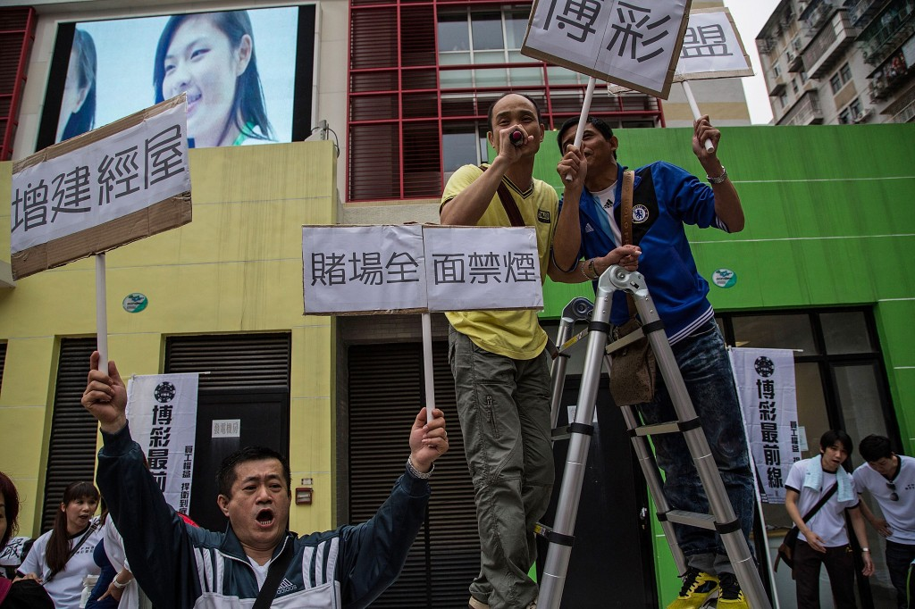 Protesters shout slogans and hold banners during a May Day demonstration on May 1, 2014 in Macau, China. Hundreds of protesters attended a march against job shortages and living conditions on May Day. Photo by Lam Yik Fei/Getty Images