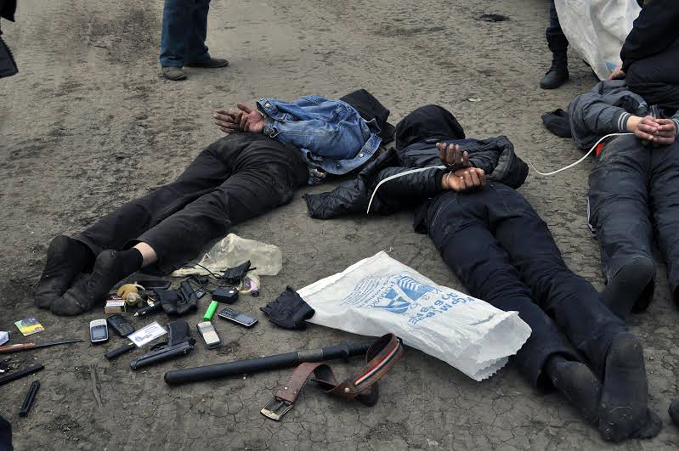 Four pro-Russian militants lay on the ground with hands tied after being arrested on suspicion of the implementation of MANPADS (Man-portable air-defense systems ) shots to a helicopter of the Ukrainian forces on May, 2, 2014 at a checkpoint near Slavyansk . Ukraine's defence ministry on Thursday raised the toll during an assault on the rebel-held town of Slavyansk to two of its helicopters shot down and two servicemen killed. Authorities say the pro-Russian insurgents used shoulder-launched rockets to bring down the two Mi-24 helicopters. Earlier, the interior minister said one of those killed was a helicopter pilot. Photo by STR/AFP/Getty Images