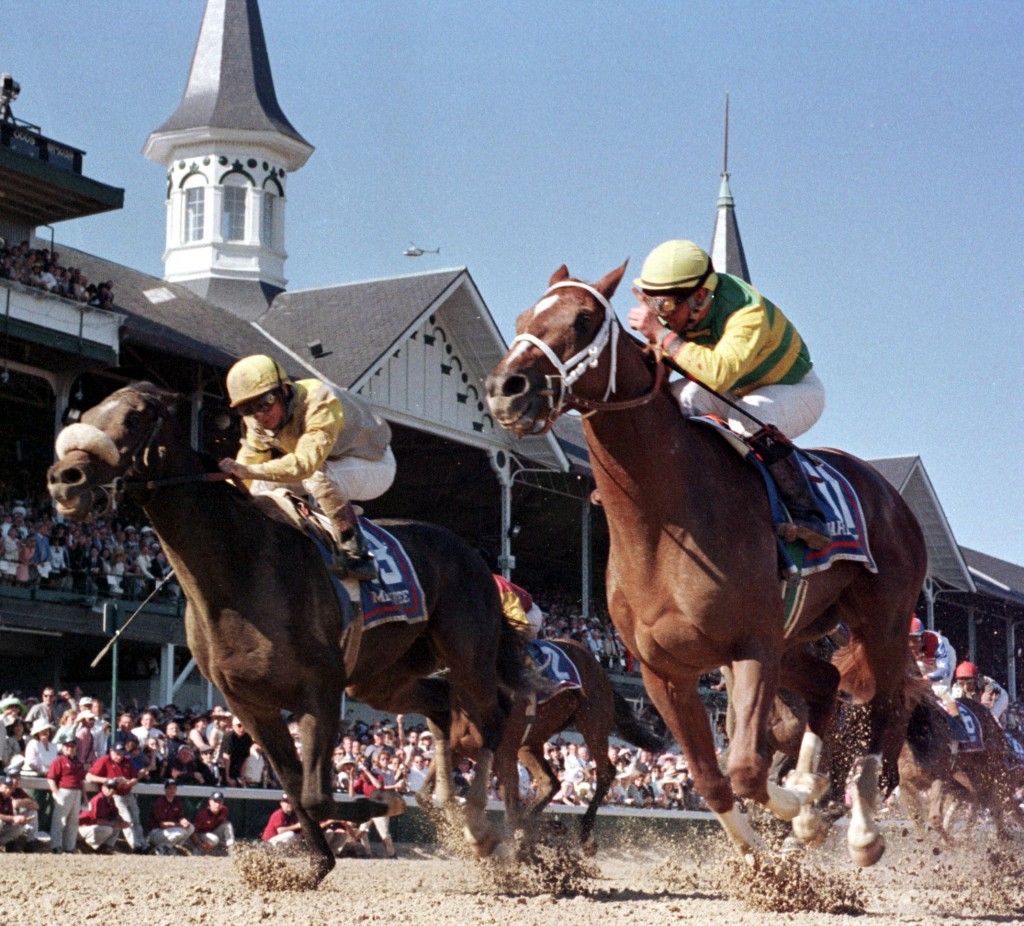 Jockey Chris Antley, on the right, aboard Kentucky Derby winner Charismatic, crosses the finish line with his finger pointing number one to second place finisher Menifee and jockey Pat Day at the 1999 Kentucky Derby. Photo by Michelle Wilkins/AFP/Getty Images