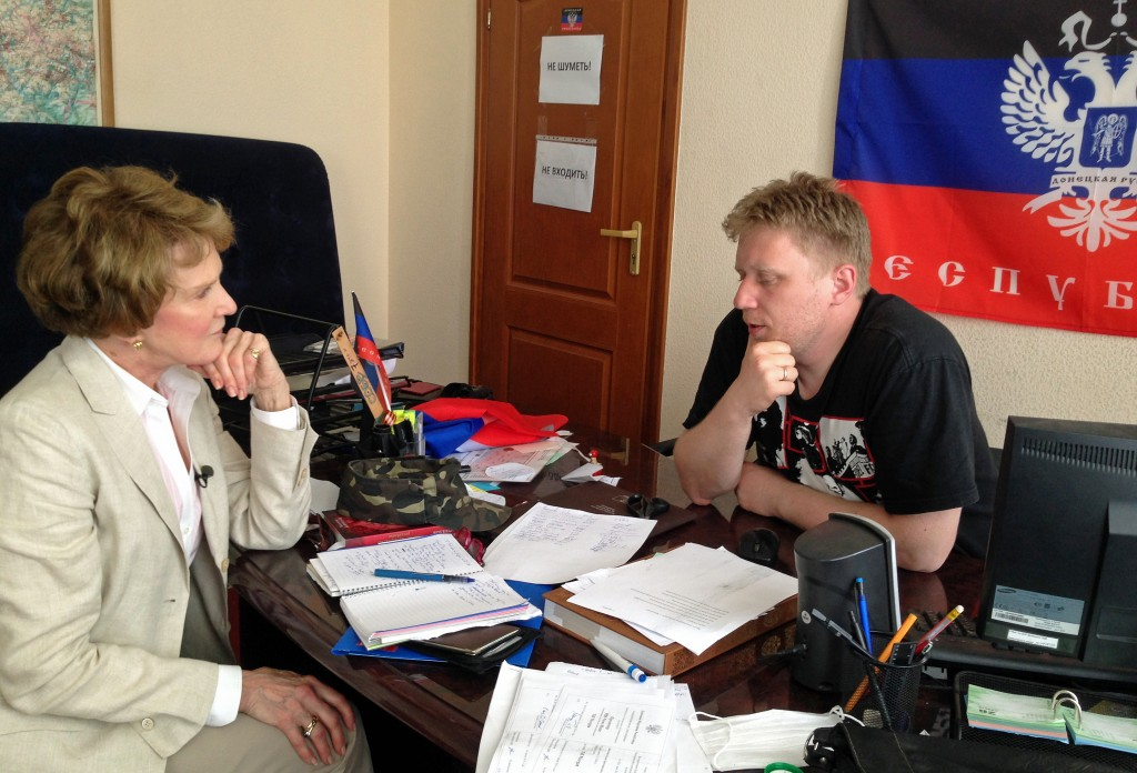 Separatists' website IT specialist Viktor Priss sits with Margaret Warner in his recently occupied office with the flag of the People's Republic of Donetsk. Photo by Natalya Gryvnyak