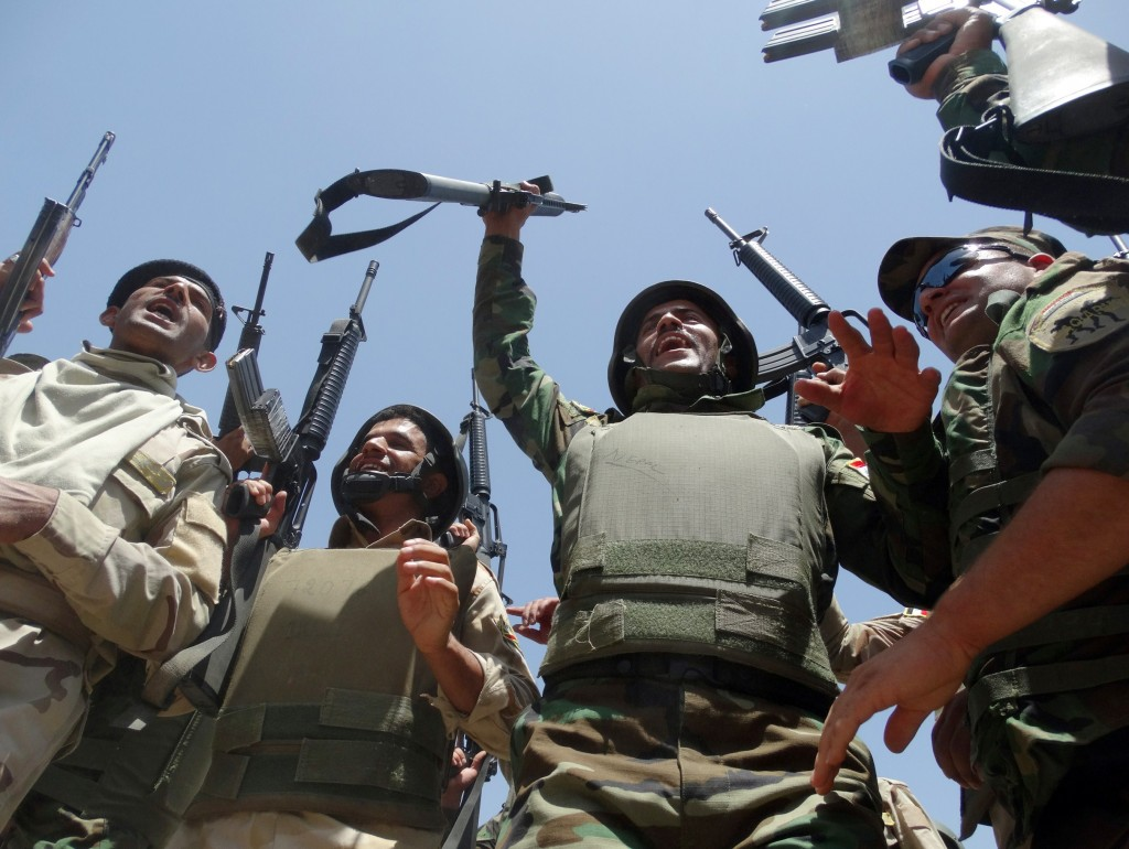 Iraqi troops raise up their weapons as they arrive to support the Sunni anti-Al-Qaeda militia Sahwa (Awakening) in its fight against anti-government militants, including from the jihadist Islamic State of Iraq and the Levant (ISIL) in the Anbar province on June 21, 2014 in the city of Ramadi, west of the capital Baghdad.  Photo:  AFP/Getty Images