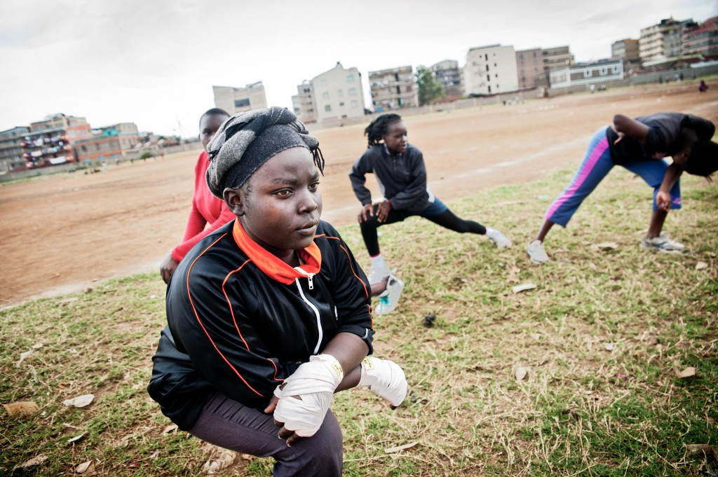 Boxgirls warm up in a field outside the community centre in Kariobangi slum. Photo by Mia Collis