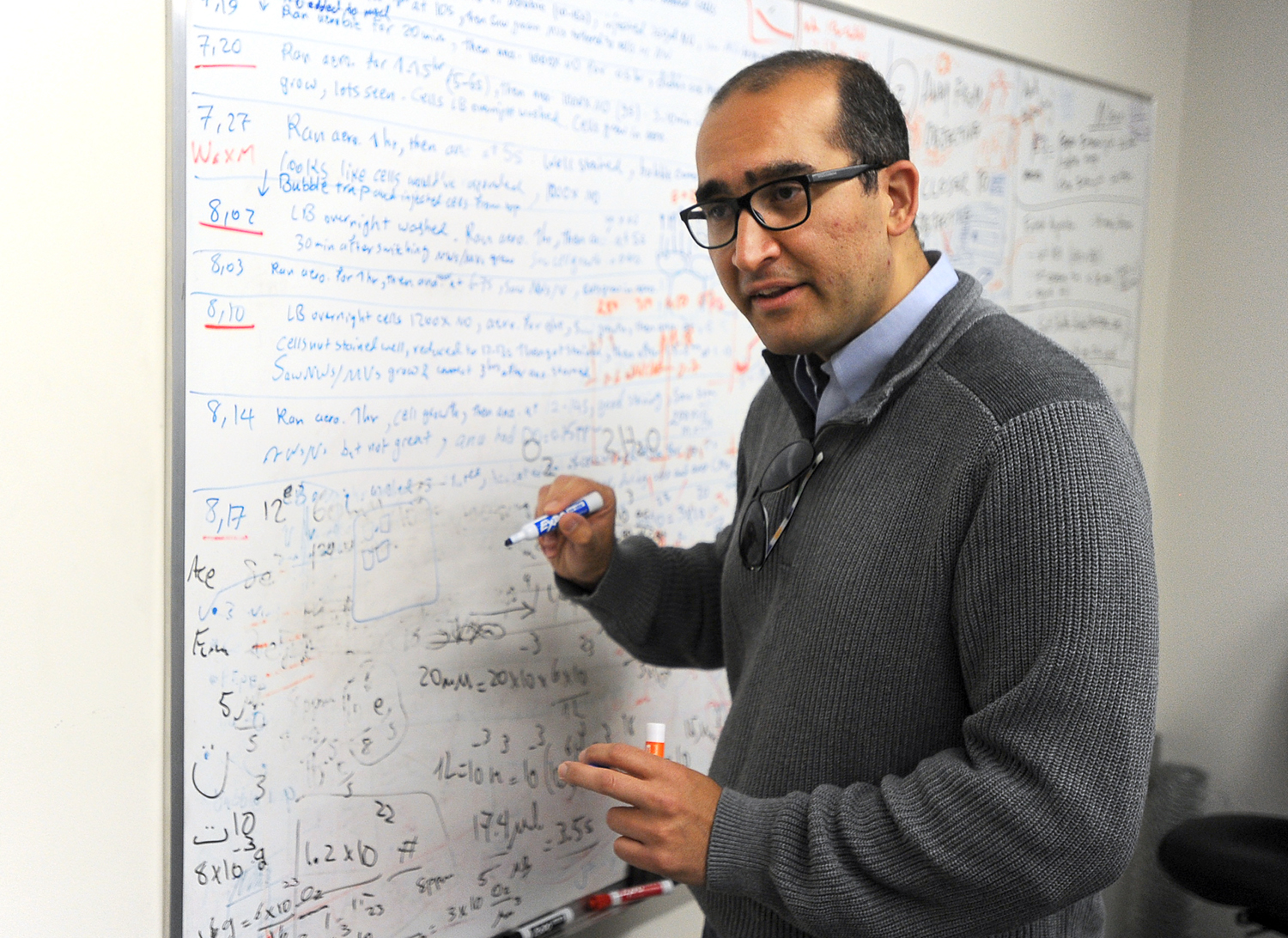 Moh El-Naggar, an assistant professor of physics at the University of Southern California, stands at the grease board where he and his team brainstorm ideas about their work involving biological electron transport. El-Naggar and other scientists at USC are doing basic research to determine how certain bacteria are able to transfer electrons great distances from themselves to other cells or inorganic minerals. Photograph by Kent Treptow for PBSNewsHour