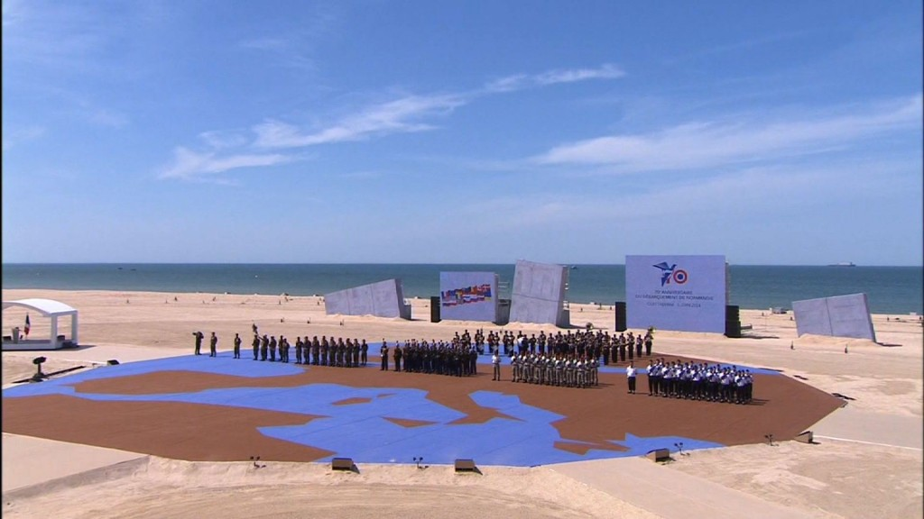Dancers march across a stage representing Europe in celebration of D-Day. Image from D-Day celebration video