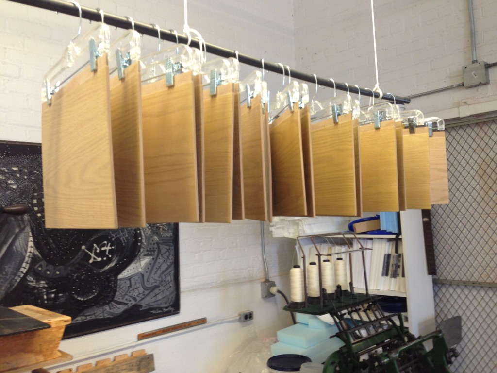 "Wooden book covers for ""Leaves of Grass,"" known as ""binding boards,"" hang to dry after being stained. Photo by Cat Wise/PBS NewsHour"