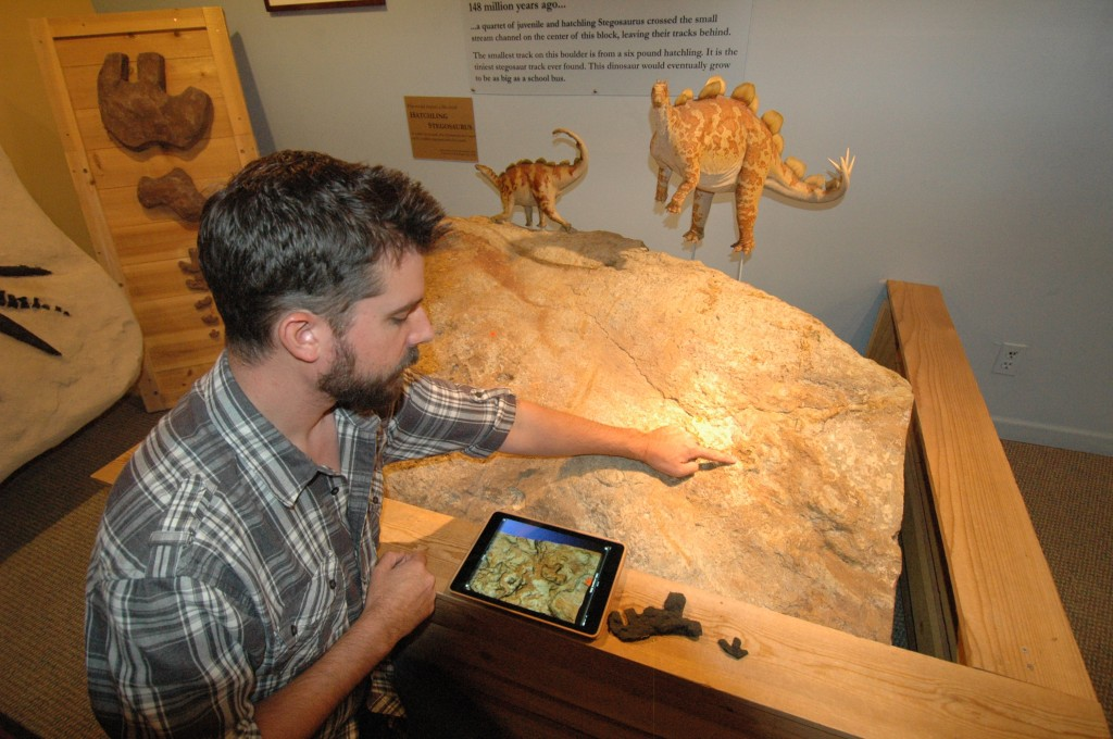 Matthew Mossbrucker, director and chief curator of the Morrison Natural History Museum, points out baby Stegosaurus tracks. Mossbrucker has found these in boulders along the highways in Morrison, Colorado. On his iPad is a 3-D model of the footprint. Photo by Rebecca Jacobson