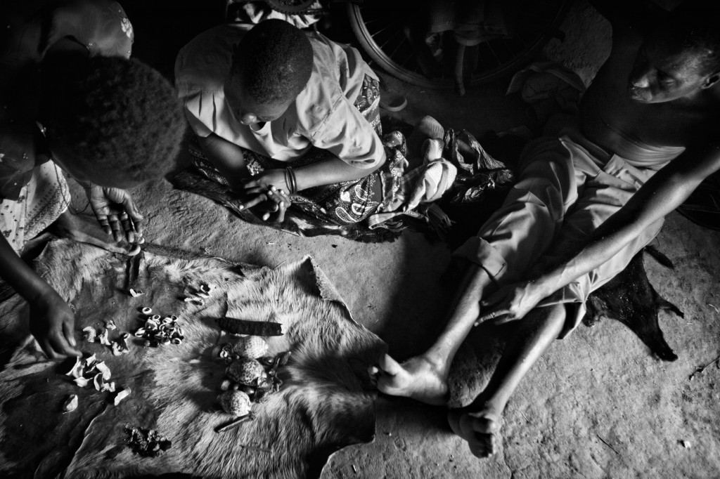 A Witch Doctor diagnoses a patient with mental illness by reading the way pieces of bone and shell fall on a goats skin. Northern Uganda. March 2011. Photo Robin Hammond/Panos