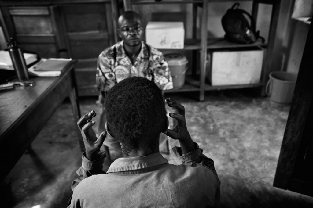 Mineyro Jean-Marie describes to Médécines Sans Frontières Psychologist Serge Nzuya Mbwibwi how he felt when The Lord's Resistance Army attacked his family and attempted to kidnap his daughter. Niangara, Democratic Republic of Congo. June 2011. Photo Robin Hammond/Panos