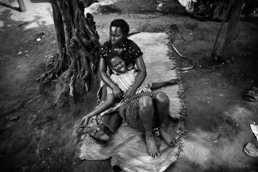 A chained patient awaits treatment at the clinic of traditional healer Dr Serwadda Hassan. April 2011. Kampala, Uganda. Photo Robin Hammond/Panos