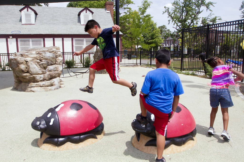 Children who attend summer camp at Park View Recreation Center in downtown Washington enjoy playtime after lunch. Six-year-old Jacob Portillo shows off his leaping skills for the camera and friends. Photo by Margaret Myers/NewsHour