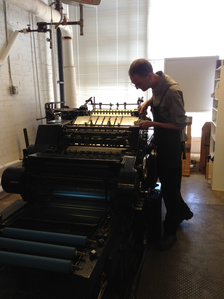 Arion printer Blake Riley oils one of Arion's historic printing presses. Photo by Cat Wise/PBS NewsHour