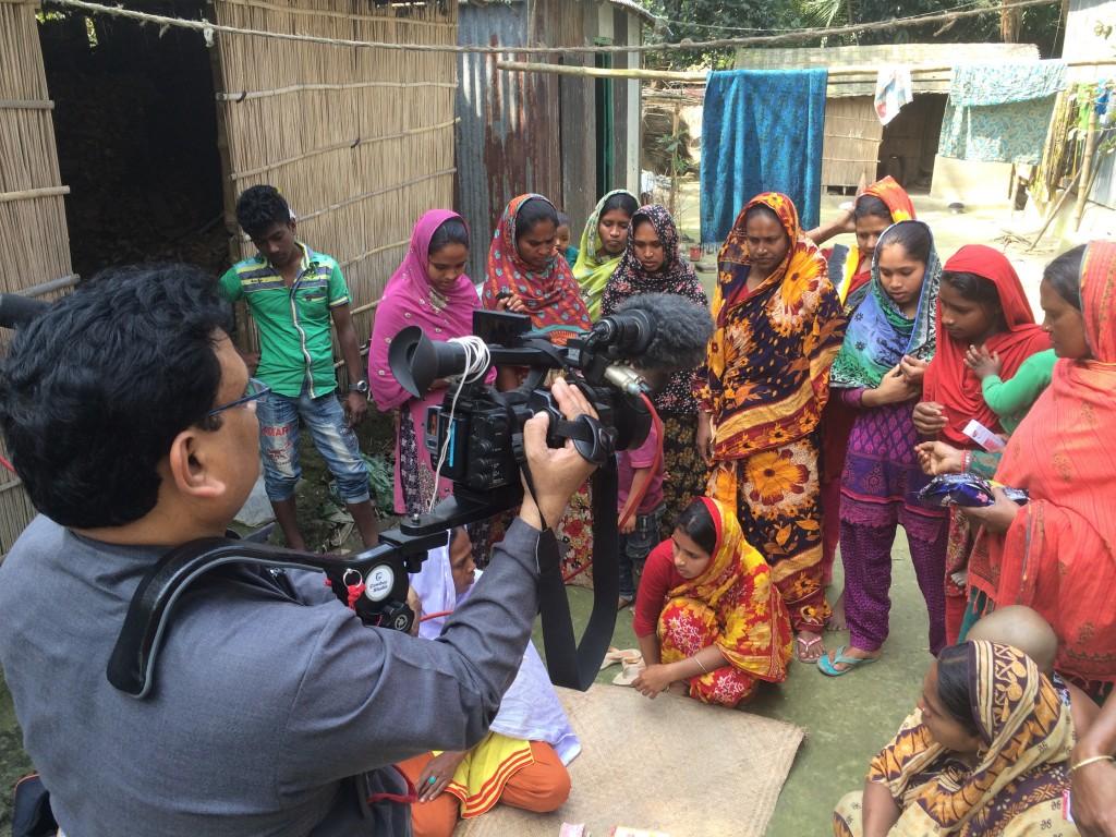Cameraman Rakesh Nagar films women in a Bangladeshi village. Photo by Fred de Sam Lazaro/PBS NewsHour