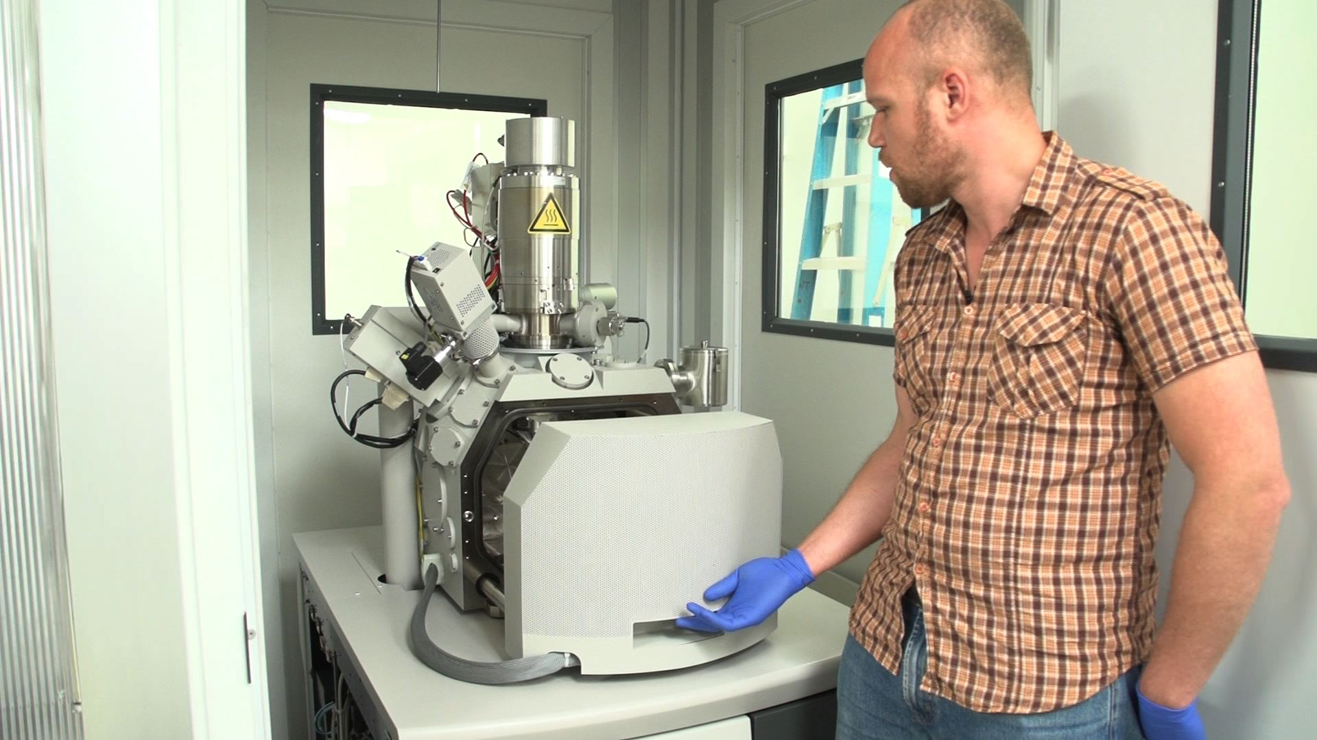 Post-doctoral researcher Chris Harris at the National Institute of Neurological Disorders and Stroke opens the electron microscope, which he uses to examine each neuron in the brain in high resolution. Photo by Rebecca Jacobson