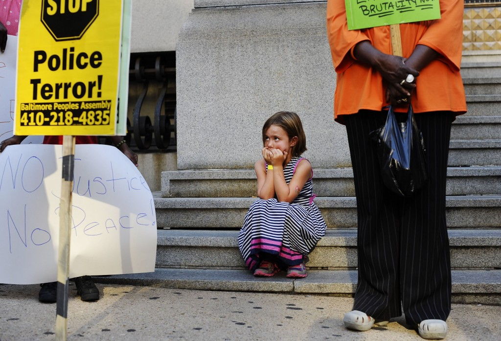 And in Baltimore on August 14, Amelia Vitek, 6, looks up at protestors and signs outside of the Clarence Mitchell Jr. Courthouse. Photo by Rachel Woolf/Baltimore Sun/MCT via Getty Images)