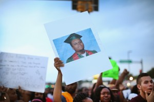 A protestor holds a photograph of Michael Brown during a 2014 protest in Ferguson, Missouri. Photo by Scott Olson, Getty Images News.