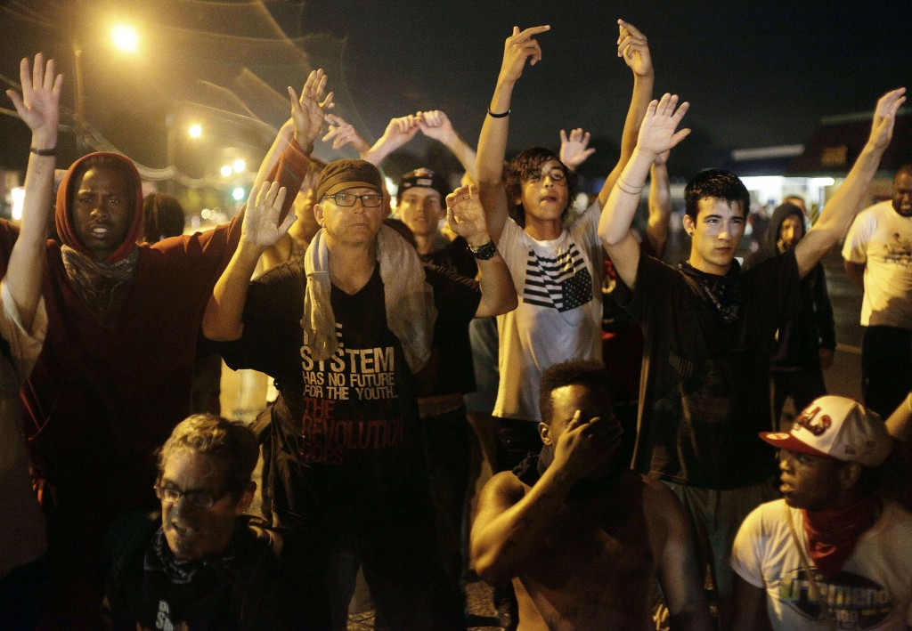 Demonstrators protest by holding their hands up while gathered on the streets of Ferguson, Missouri, late on Aug. 16. A crowd of some 200 demonstrators defied a curfew that came into effect early on Aug. 17. Photo Joshua Lott/AFP/Getty Images