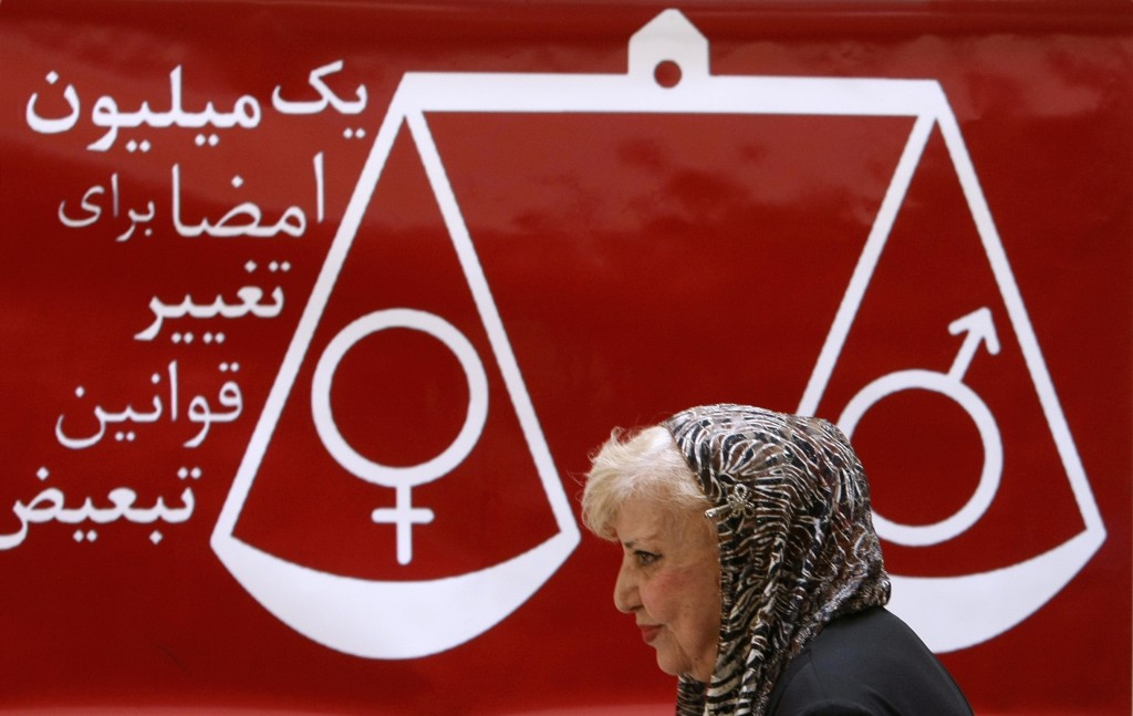 """Iranian poet and women rights activist Simin Behbahani walks past a banner reading """"one million signatures to change the biased laws"""" and bearing a scale balancing female and male symbols during a press conference in Tehran. Photo by Behrouz Mehri/AFP/Getty Images)"""