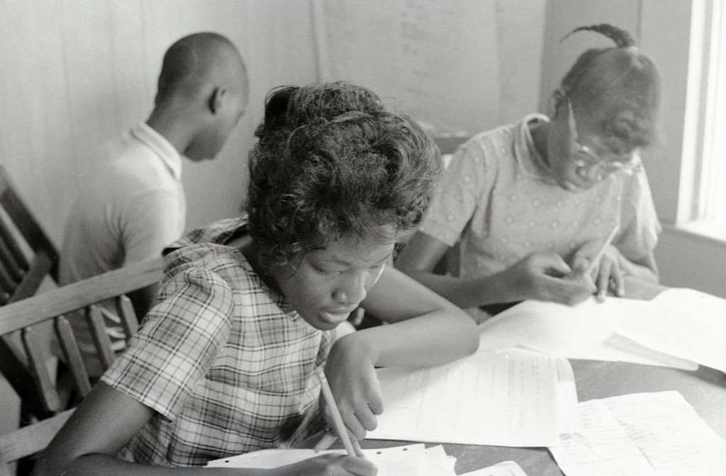 Students Margaret Dwight (left) and Alice Dwight (right) writing at their desks in the Freedom School at Mt. Zion Baptist Church in Hattiesburg, Mississippi. Photo by Herbert Randall from Herbert Randall Freedom Summer Photographs collection, McCain Library and Archives, the University of Southern Mississippi.