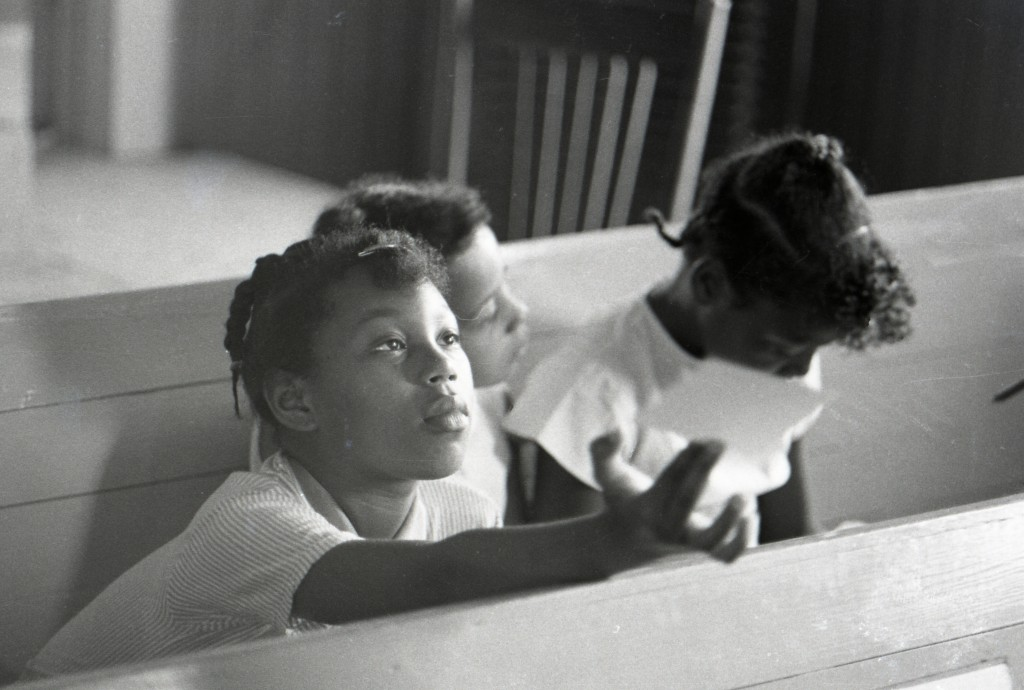 Three young African-American girls sitting together during a Freedom School class at Mt. Zion Baptist Church in Hattiesburg, Mississippi, during Freedom Summer 1964. Photo by Herbert Randall from Herbert Randall Freedom Summer Photographs collection, McCain Library and Archives, the University of Southern Mississippi.