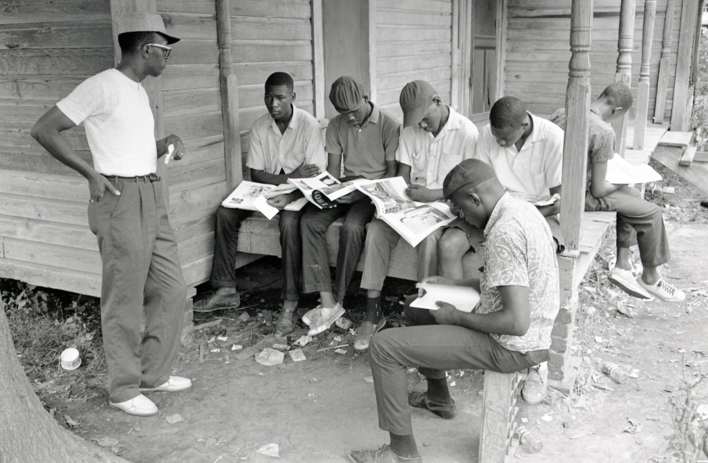 A group of teenaged male Freedom School students sitting on and near the porch of a house on Gravel Line Street reading issues of Ebony magazine. Volunteer Arthur Reese (school principal from Detroit, Michigan), co-coordinator of the Freedom Schools in the Hattiesburg project, stands talking to them. Photo by Herbert Randall from Herbert Randall Freedom Summer Photographs collection, McCain Library and Archives, the University of Southern Mississippi.