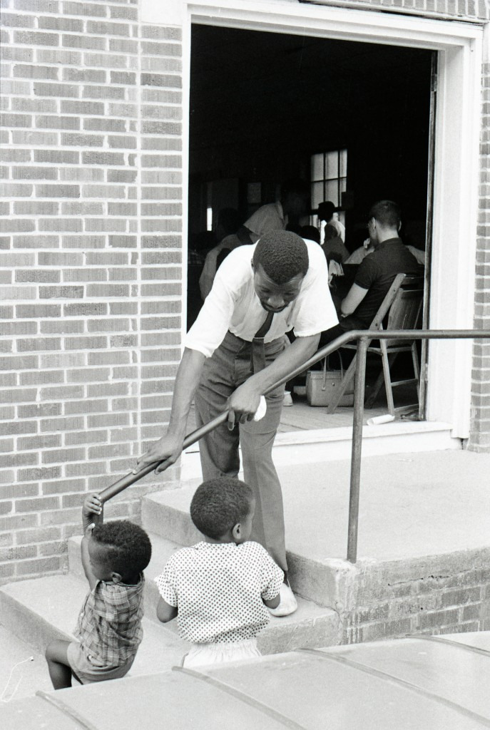 Volunteer William D. Jones (native of Birmingham, Alabama, and New York public school teacher), who taught in the Freedom School at True Light Baptist Church in Hattiesburg, leaning on the stair rail of St. John United Methodist Church in Palmers Crossing talking with local child Tilton Sullivan. Photo by Herbert Randall from Herbert Randall Freedom Summer Photographs collection, McCain Library and Archives, the University of Southern Mississippi.