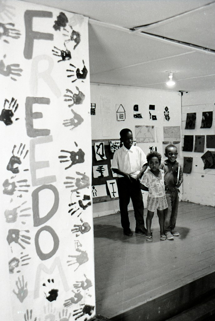 "Three local African American children standing in the exhibit area of the Palmers Crossing Community Center where Freedom School students' artwork is on exhibit. The large sign with handprints down the left wall spells ""Freedom."" Photo by Herbert Randall from Herbert Randall Freedom Summer Photographs collection, McCain Library and Archives, the University of Southern Mississippi."