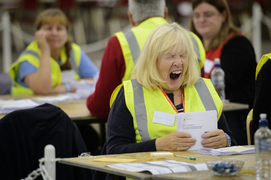 A woman shows signs of fatigue as she counts ballot cards at the Royal Highland Centre counting hall in Edinburgh, Scotland on September 19, 2014, after ballot counting got underway in the referendum on Scottish independence. In counting centres, jam-packed pubs and living rooms across Scotland, voters were nervously waiting for the results of their historic vote on whether or not to leave the United Kingdom. AFP PHOTO/LEON NEAL (Photo credit should read LEON NEAL/AFP/Getty Images)