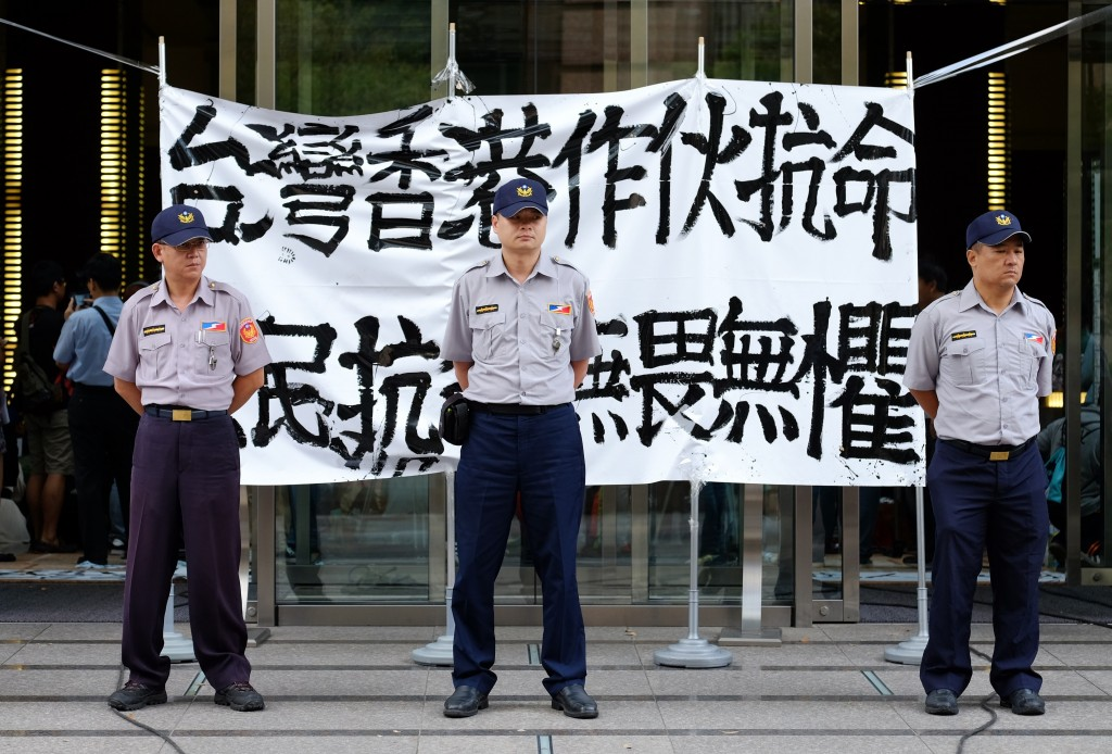 """Policemen stand guard in front of a poster reading """"Taiwan, Hong Kong people should join together to disobey orders"""" at the lobby of the Hong Kong office in Taipei, the capital of Taiwan, on Sept. 29. Photo by Sam Yeh/AFP/Getty Images"""