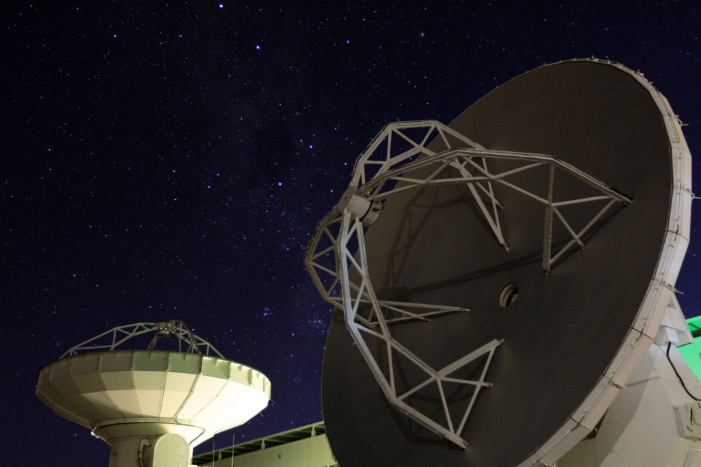 Two ALMA antennas facing different parts of the cloudless night sky. Photo by Joshua Barajas/PBS NewsHour