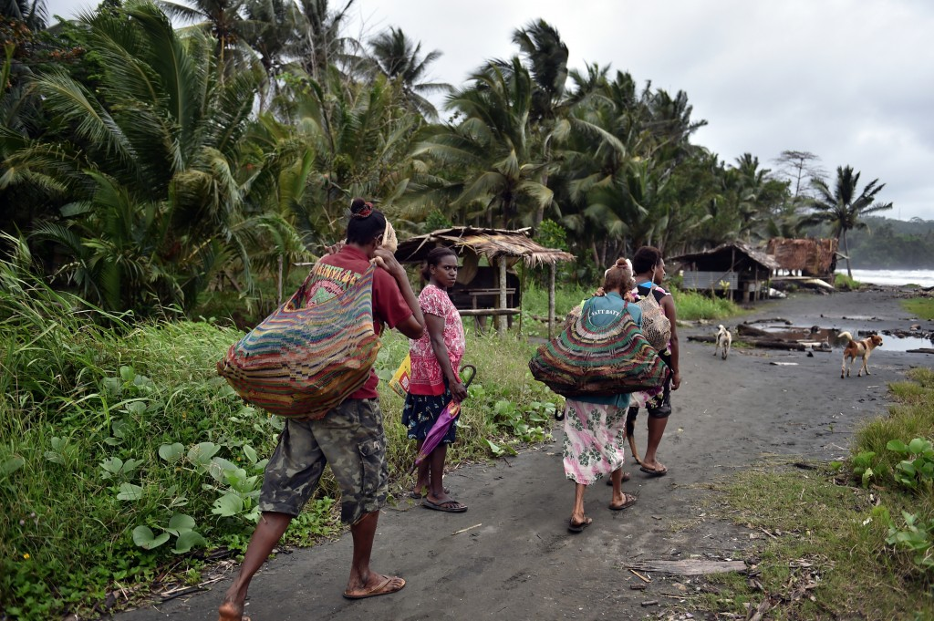 Women carry wood in the town of Kerema, Papua New Guinea, on Sept. 5. Rising sea levels are forcing residents of the island nation's smaller atolls to move to the mainland. Photo by Aris Messinis/AFP/Getty Images