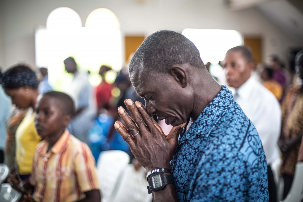 A man prays for those who died of Ebola at St. Joseph Parish Catholic Church in Monrovia, Liberia on Oct. 12, 2014. Photo by Mohammed Elshamy/Anadolu Agency/Getty Images